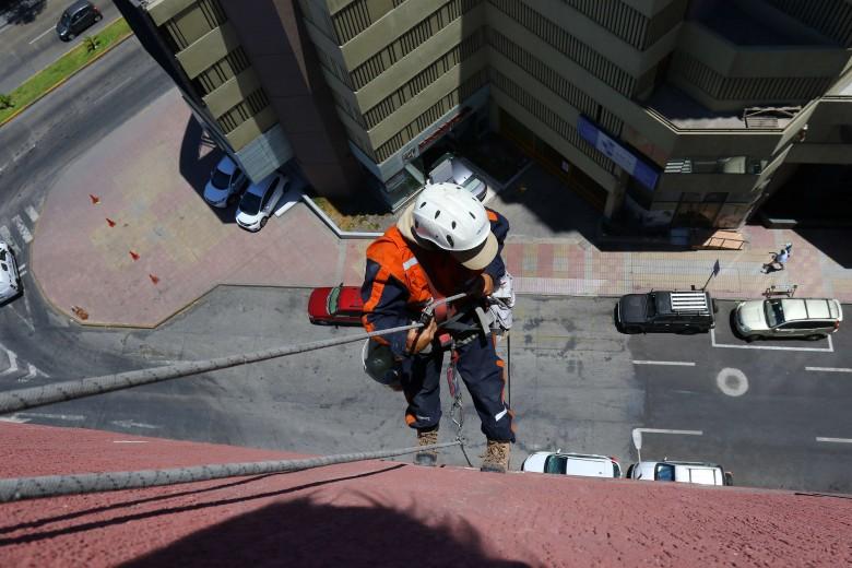 Un trabajador en altura limpia las ventanas del edificio Pukara. Foto: Matías Quilodrán.