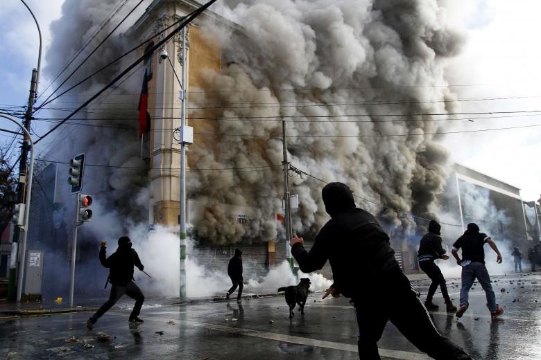 Un muerto como resultado del incendio provocado en farmacia de Las Heras con P. Montt, y otros dos locales quemados y dos más saqueados, luego de la marcha del 21 de mayo.